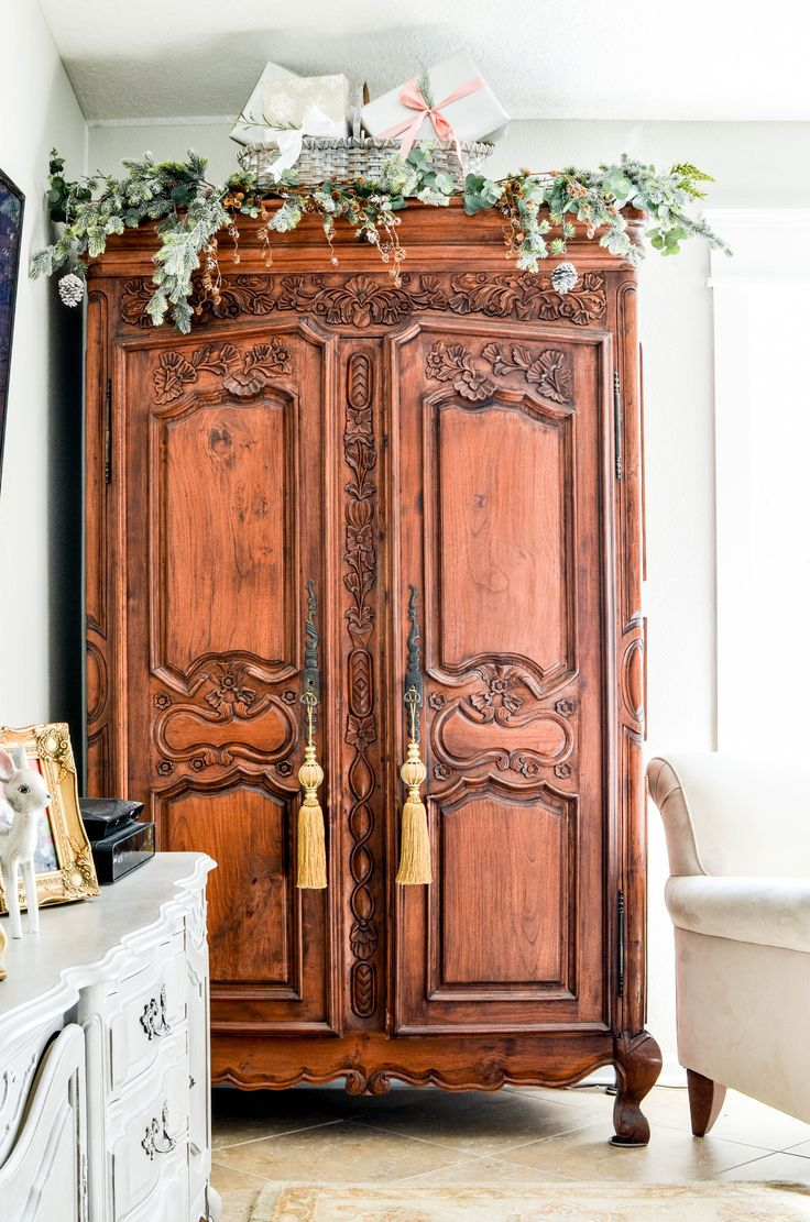 French country Christmas decor - add faux greenery to the top of your armoire. Simple and elegant!