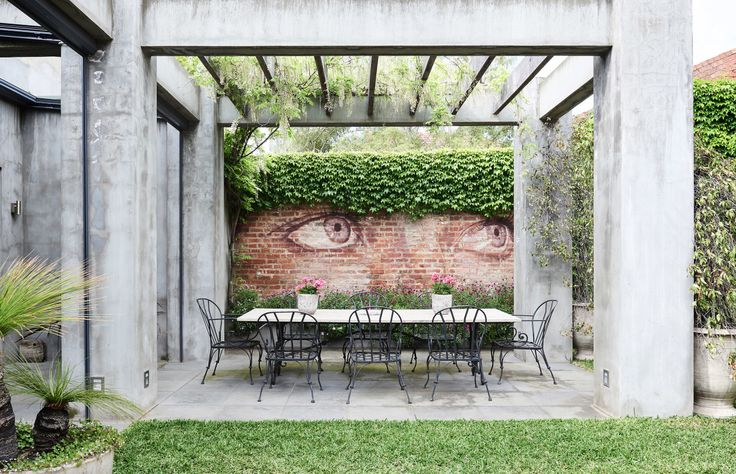 Outdoor dining area, eyes by artist Rone. Photo – Eve Wilson. Production – Lucy Feagins / The Design Files.