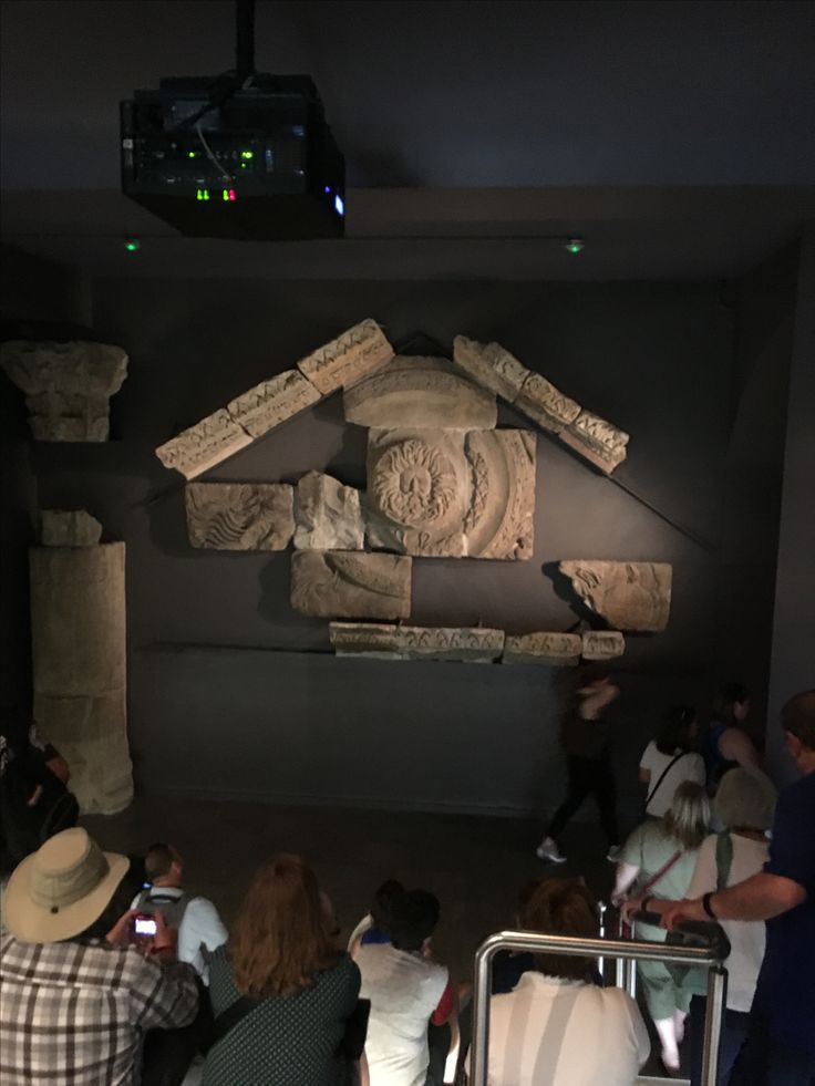 students studying the great ornamental pediment thought to be the Gorgon's Head which was a powerful symbol of the goddess Sulis Minerva. #bath #romanbaths