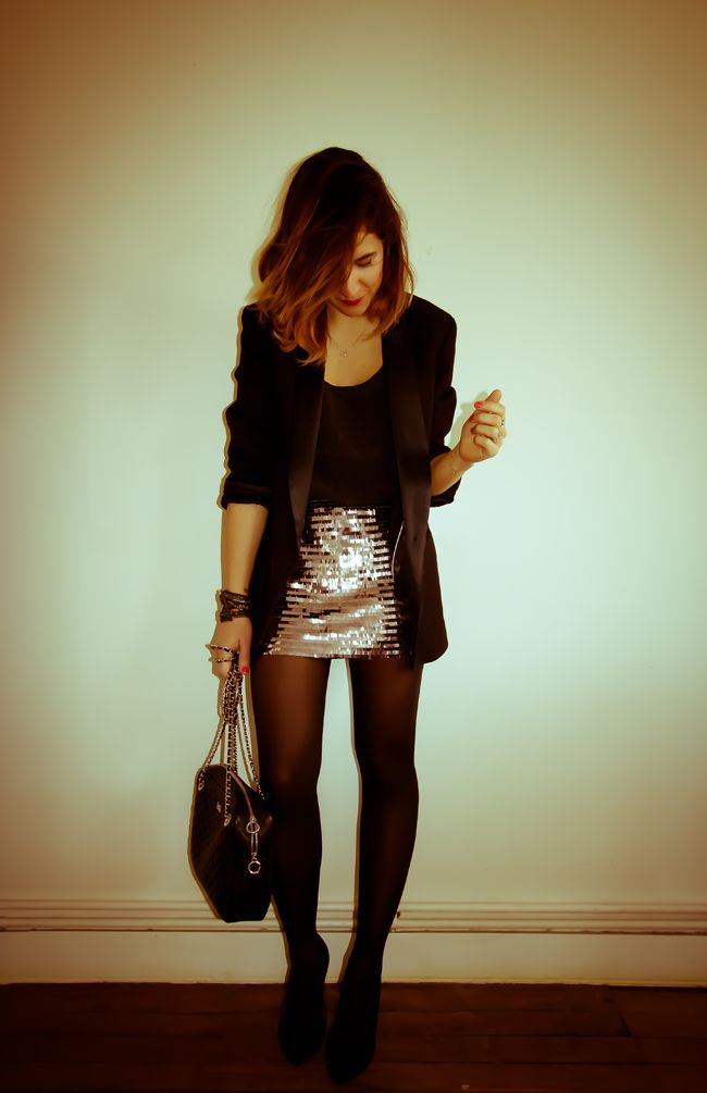 Tee-shirt noir + jupe grise à sequins + collants noirs opaques + blazer noir + bottines à talons noires