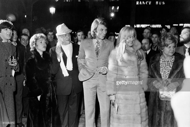 French singer Jacques Higelin (L), French writer Henri Charriere (3-L), french singer Johnny Hallyday (C) and his wife Sylvie Vartan (2nd R) arrive for the premiere of the film 'Popsy Pop' directed by Jean Herman on March 10, 1971 in Paris.  r /