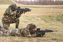XM8 testing; One operator is kneeling with an XM8 Carbine and a XM320 (a 40 mm grenade launcher) attached, while the other uses the XM8 sharpshooter (designated marksman) variant.