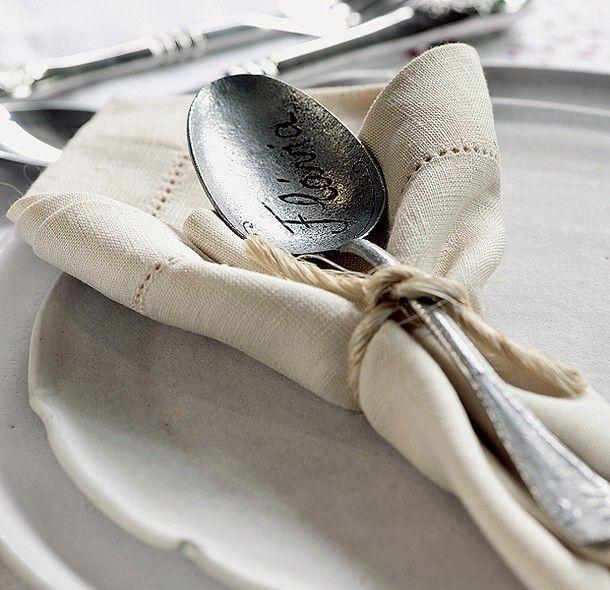Uma tira de ráfia amarra a colher personalizada, com o nome do convidado, ao guardanapo