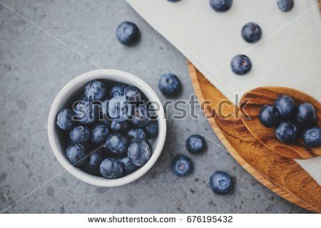 Top view of organic fresh blueberries with wooden spoon for breakfast meal