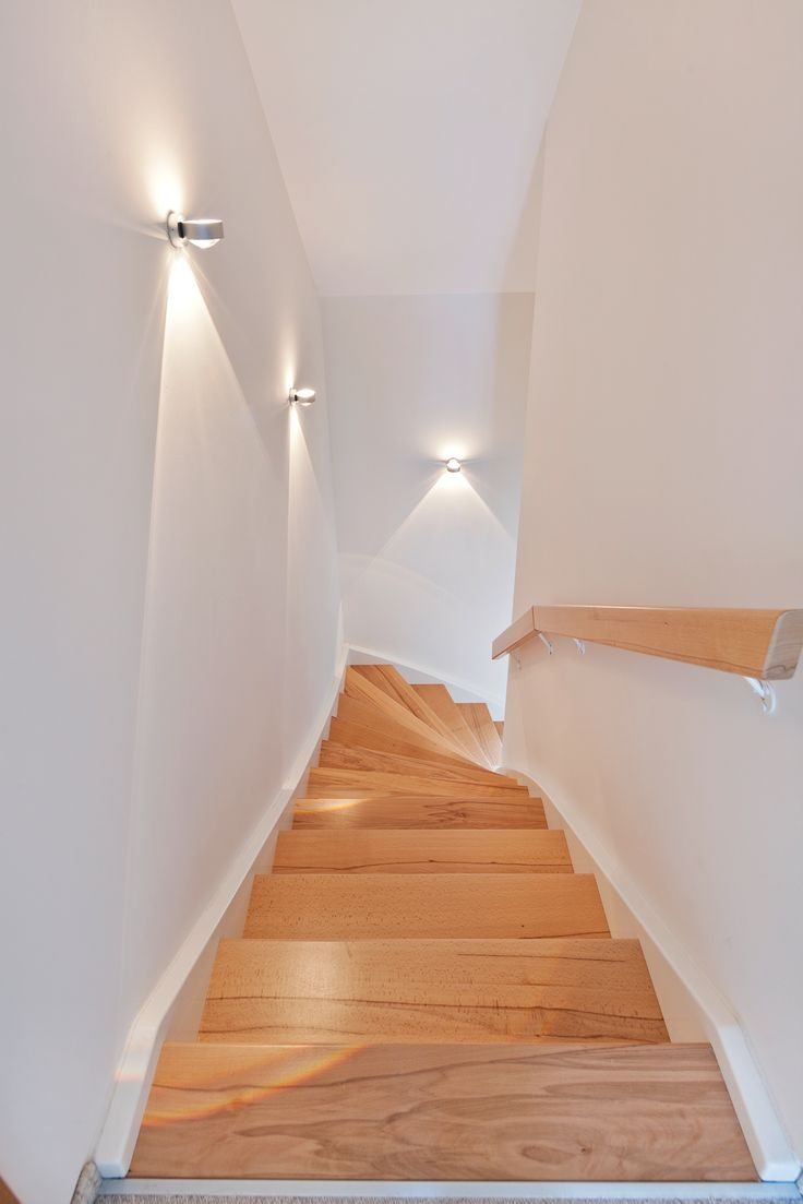 Natürliche Treppenstufen mit dezenter Beleuchtung der weißen Wand.