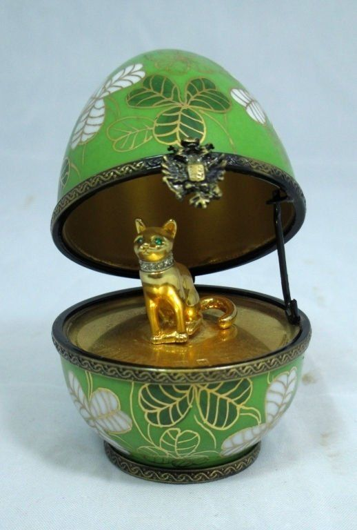 """Faberge - Clover Egg Faberge porcelain egg with Clover Leaf surprise This egg is handcrafted in Limoges France. 24K gold plated Cat surprise Egg is signed and numbered Measures 2.5"""" Tall"""