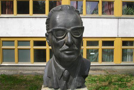 Busto al presidente Salvador Allende, en la entrada de la escuela del mismo nombre, en la calle Pablo Neruda en Berlín.    La escultura, en bronce, inaugurada el año 1977, es una realización de la artista alemana Ingeborg Hunzinger.  Color gris y textura rugosa