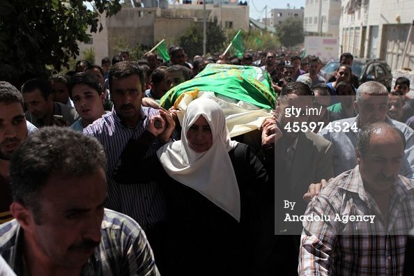 Caption:HEBRON, WEST BANK - SEPTEMBER 23: The mother (C) of Amer Abu Aisha, killed by Israeli troops, carries her son's body during his funeral in the West Bank town of Hebron on September 23, 2014. Amer Abu Eisha and Marwan Qawasmeh whom Israel had accused of carrying out the kidnapping and murder of three Israeli teenagers in June, were killed 'in exchange of fire' in Hebron, southern West Bank. (Photo by Mamoun Wazwaz/Anadolu Agency/Getty Images)