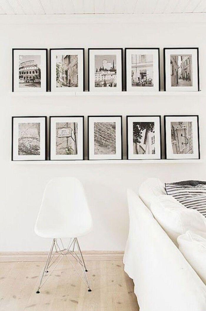 Stijlvolle zwarte lijsten op 2 planken aan de muur. De gelijke lijsten met sepia foto's passen perfect bij het witte interieur en de prachtige houten vloer. Een fotomuur past in elk interieur.