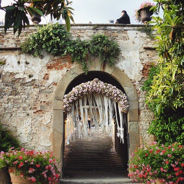 At the ultimate Italian destination wedding, an archway full of flowers in Tuscany. Event Planner: SposiamoVi Florist: By Appointment Only Design Venue: Fattoria di Maiano