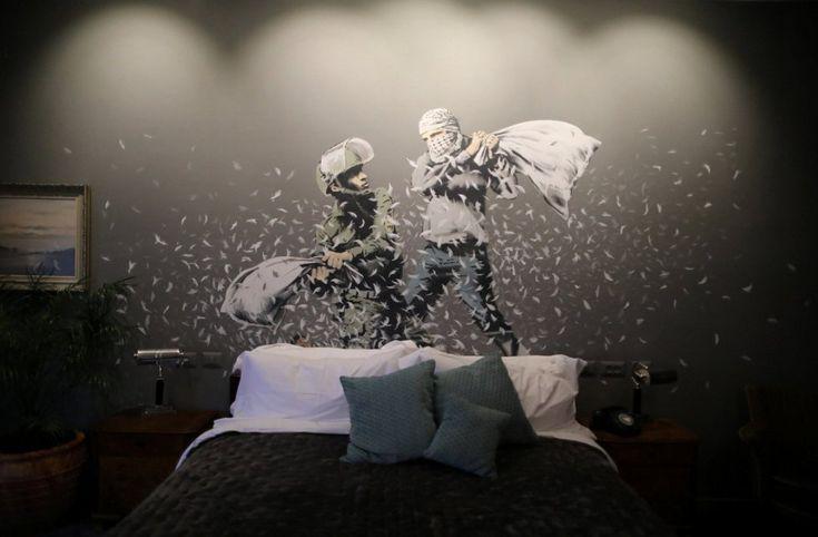 Banksy ha decorado las salas del hotel 'The Walled Off' que este viernes abrió sus puertas para los medios en Belén, en Cisjordania, y cuyas habitaciones tienen vistas al muro de separación construido por Israel. En la imagen, un grafiti del artista Banksy muestra a un soldado israelí y a un joven palestino enmascarado durante una pelea de almohadas.