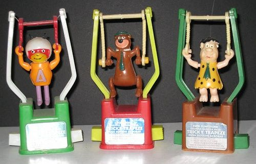 Tricky Trapeze toys.. squeeze the buttons on the side and they do flips! Everyone had these!  They only cost about 19 cents.