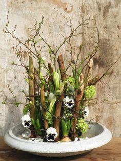 Bloeiend hout,  In een frame van takken worden voorjaarsbloemen als viooltjes, anemonen en sneeuwbal op speelse wijze verwerkt.