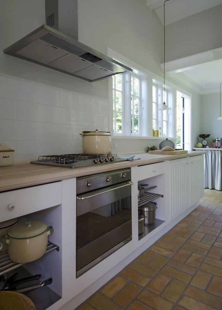 Det moderne køkken er gennemført i klassisk landlig stil, som passer til husets stil med bordplade i fyrretræ og stribet forhæng syet af gardinstof fra Ikea. Gulvet er fra Prøvelyst Teglværk i Hillerød og har indlagt gulvvarme.