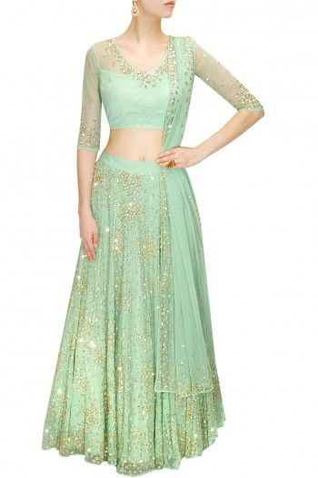 Astha Narang Featuring a mint green shimmer flared lehenga in net heavily embroidered with sequins and beads work in floral pattern.  It is paired with matching embroidered net blouse with cut-out detailing at back.  It also comes along with mint green sequins and beads embroidered net dupatta.