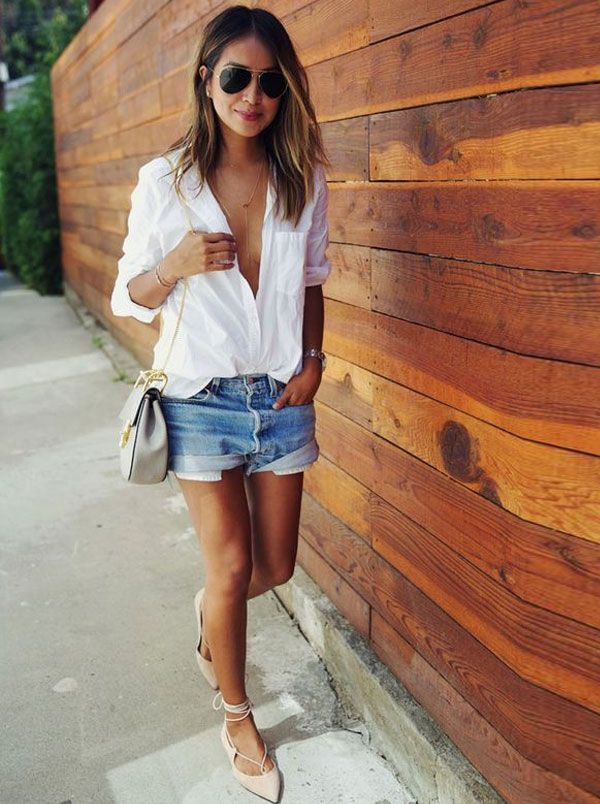Julie Sariñana com shorts jeans, camisa decotada e sapatilha de amarração.