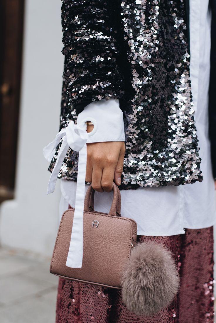 Nina Schwichtenberg trägt einen schwarzen Pailletten Blazer, einen rosa Rock ebenfalls mit Pailletten, dazu eine weiße lange Bluse & als Accessoire die Aigner Mini Bag mit Puschel. Mehr auf www.fashiioncarpet.com