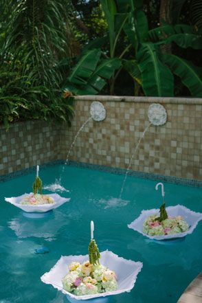 What a great idea ! Floral umbrella pool wedding decor. Battery operated lights could be added for a elegant ambiance in the evening.