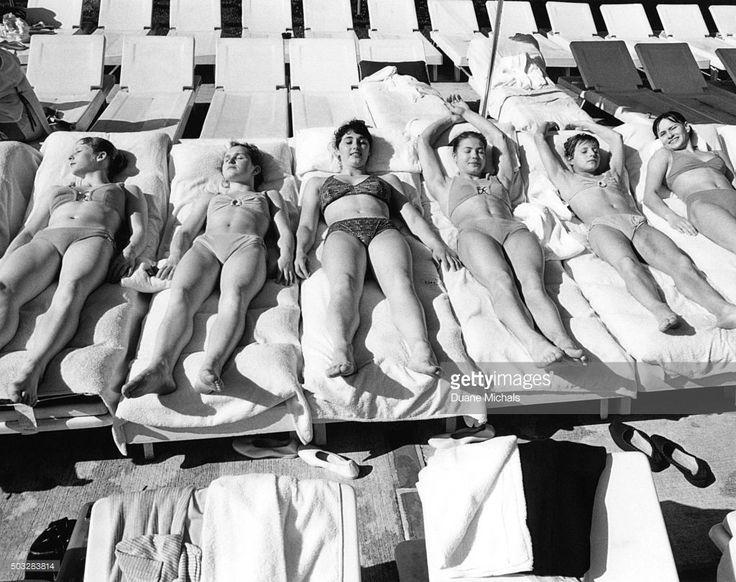 Russian Women's Olympic Gymnastics Team wearing bikinis, relaxing in sun on row of deck chairs in Miami: (left to right) Tamara Lazakovich, Antonina Koshel, Liubov Bogdanova, Liudmila Turishcheva, Olga Korbut, Rusiko Sikharulidze.