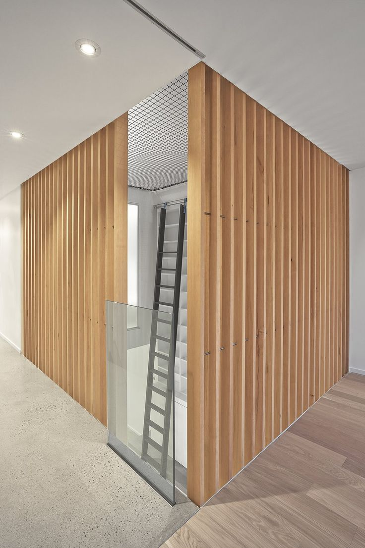 The atrium is 'enclosed' at the second floor level by vertical grain douglas fir slats.  The trapeze net play surface on the third floor can be seen. Photo 7 of Atrium Townhome modern home