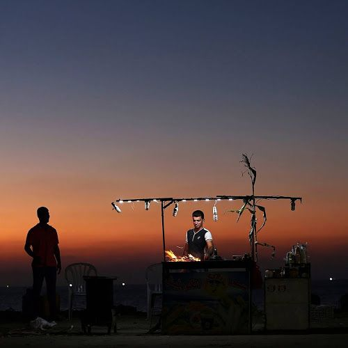 A Palestinian man cooks corn on a beach at sunset in Gaza