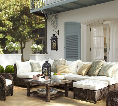 source: Pottery Barn    Pretty, Mediterranean style patio. Woven sectional seating, armchair and coffee table. Assorted blue pillows, woven rug and candle lantern lighting.