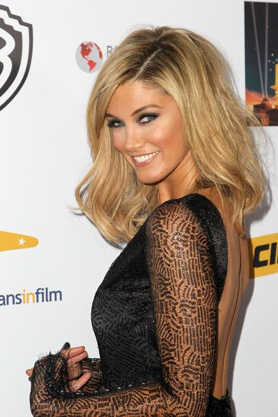 Delta Goodrem with long blonde hair, arriving at the Australians in Film Awards Gala