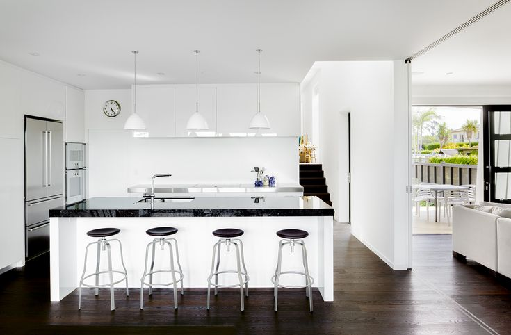 A great example of how white-on-white can look so stylish and soothing, this kitchen in a house designed by Archaus Architects uses Resene Half Sea Fog throughout, on walls, cabinets and ceilings. The black benchtop offers a sleek contrasting elements.