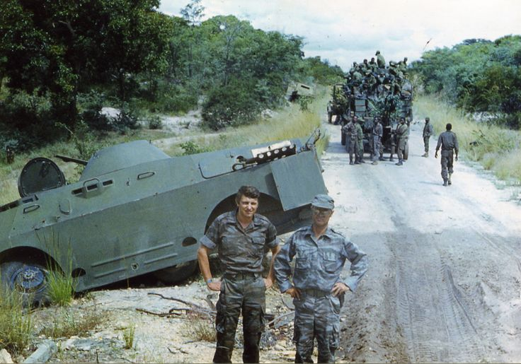 """A pair of Soviet officers pose on """"The Road of Life or Death"""" somewhere between Menongue and Cuito Cuanavale. Date sometime in 1988."""