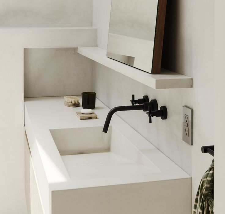 custom geometric white plaster sink in brooklyn bathroom The wall ledges and sink were custom General Assembly designs. The faucet is from Brooklyn manufacturer Watermark.