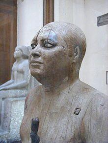 El titulo: Sheik-el-Beled (El alcalde del pueblo) fue tallada en época del Imperio Antiguo de Egipto, durante la Dinastía V de Egipto.  Autor: Auguste Mariette Material: escultura de madera (Museo Egipcio de El Cairo)