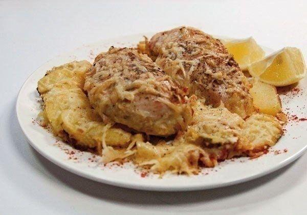 Куриные грудки, запеченные в сливках под сыром.   Куриное филе  2 зубчика чеснока, которые желательно разрезать вдоль на небольшие кусочки.  3-4 ложки перетертых консервированных помидоров  Половина лимона.  100 г. сливок жирностью не менее 20 процентов  2-3 небольших картофелин для гарнира  100 г. любого сыра  Ложка растительного масла  Одна средняя луковица  Немного соли и черного молотого перца