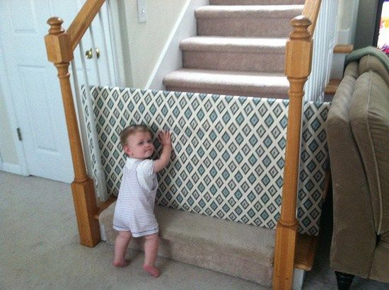 Easy DIY Baby Gate for stairs - plywood, batting (and/or foam) , cute fabric, staple gun. Just slide it through the slats