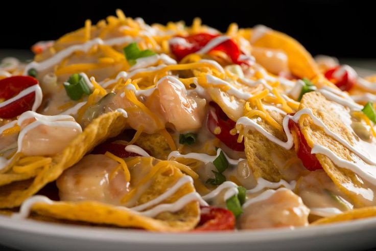 Seafood nachos: Nachos topped with shrimp, crawfish and lobster and garnished with white queso sauce, red jalapenos, green onions, cheddar cheese and sour cream: http://abcn.ws/1wytPbN