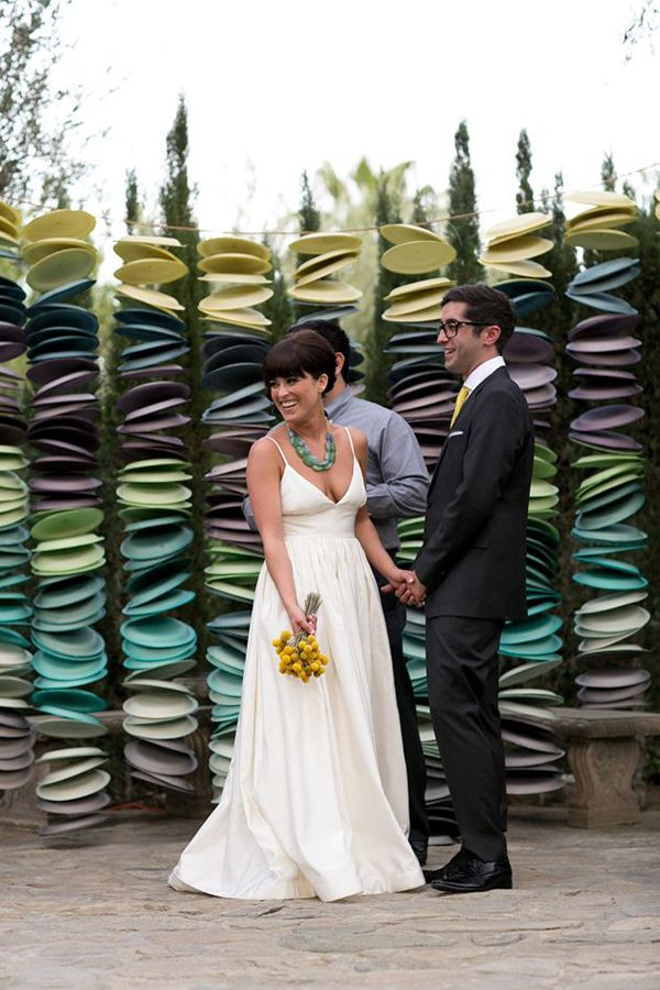 DIY Garland: This clever backdrop is made of (you'll never guess!): paper plates. This crafty bride painted hundreds of plates in their wedding colors, punched a hole in the middle of each one, and strung them together to create this modern display for their outdoor ceremony.