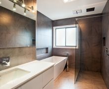 Floor to ceiling 600x600mm tiles. Freestanding bath with floor-mounted outlet & inset tiled shelf. Walk-in shower with ceiling-mounted shower head. Wall-hung vanity with undermount basin & wall mounted taps.