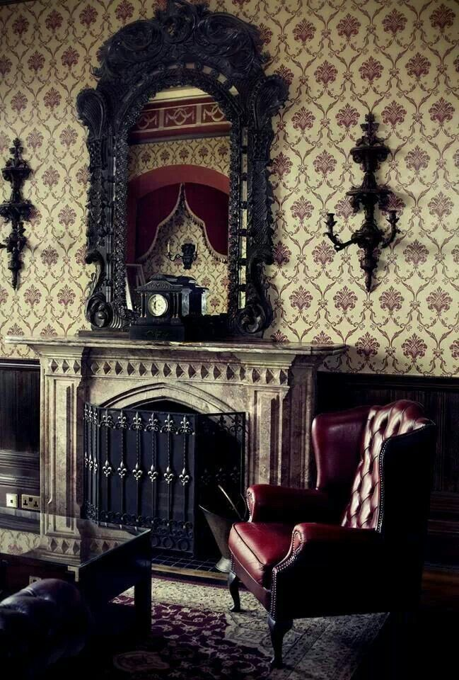 Vintage Sitting Room: Classic Victorian Gothic Style With A Oxblood Leather  Wing Back Chair, And An Ornate Black Mirror Frame And Sconces.