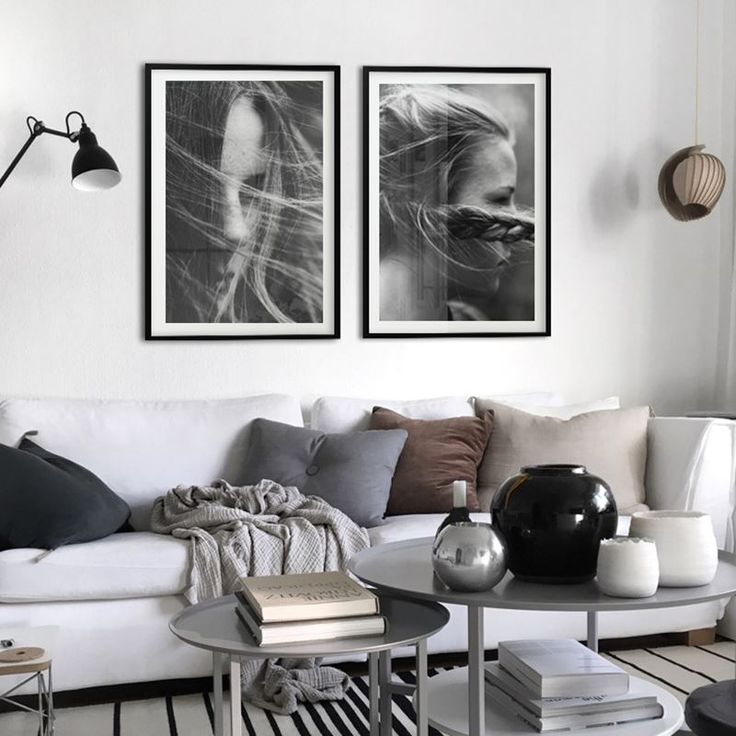 White living room in neutral color scheme, cheramic round vases and black and white framed portrait posters from printler.com, the marketplace for photo art.