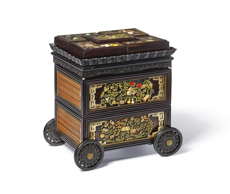 A RARE IMPERIAL INLAID AND EMBELLISHED ZITAN CARRIAGE TIERED BOX AND COVER QING DYNASTY, QIANLONG PERIOD of rectangular section, the zitan cart constructed of boxes layered on two tiers and supported on four pierced wheels inlaid with silver-wire, the shorter sides of the boxes inlaid with boxwood stripes stained to two colours within a gilt-bronze border, the longer sides of the box similarly inlaid with borders of gilt-bronze enclosing angular scrollwork flanking a meticulously arranged…