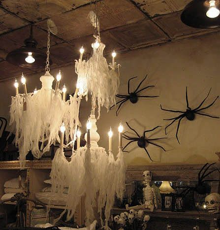 halloween decor...cheesecloth over chandelier, giant spiders on the wall