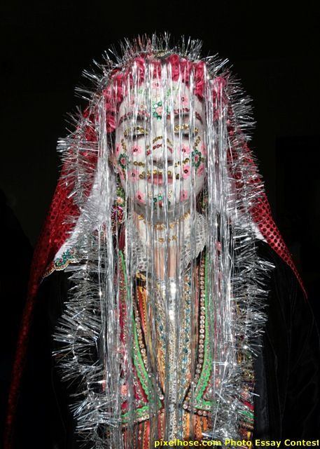 The inhabitants of the remove mountain village of Ribnovo are Bulgarian speaking Muslims referred to as Pomaks. The bride's face is covered in thick, chalky white paint and decorated with colorful sequins. A long red veil covers her hair, her head is framed with tinsel, her painted face veiled with silvery filaments. The village of Ribnovo has kept its traditional marriage ritual alive despite decades of persecution.
