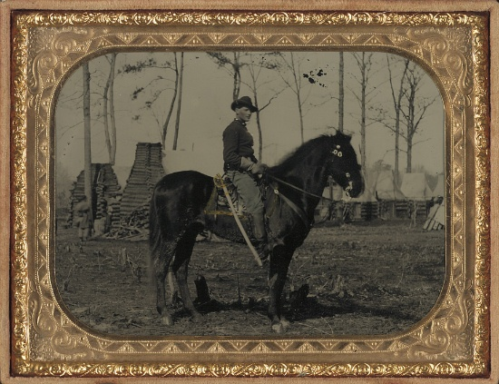 Historic Horse Photography; The American Civil War: Unidentified soldier in Union cavalry uniform, on horse, with cavalry saber, in front of encampment with winter chimneys, taken between 1861-1865, Library of Congress