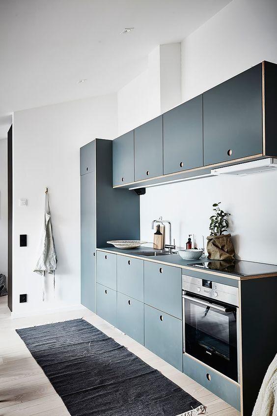 Cocina de líneas simples con estilo. Encimera del mismo material que los frentes de armario, sin tiradores.