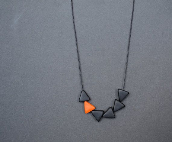 Polymer clay triangle beads in black and orange arranged in a minimalist necklace and hung on adjustable black cotton string.    Weight: 15 g