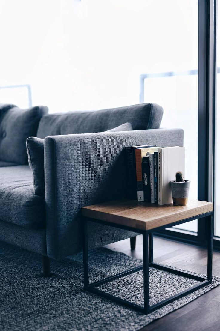 Minimal apartment with grey @article couch, wooden side table
