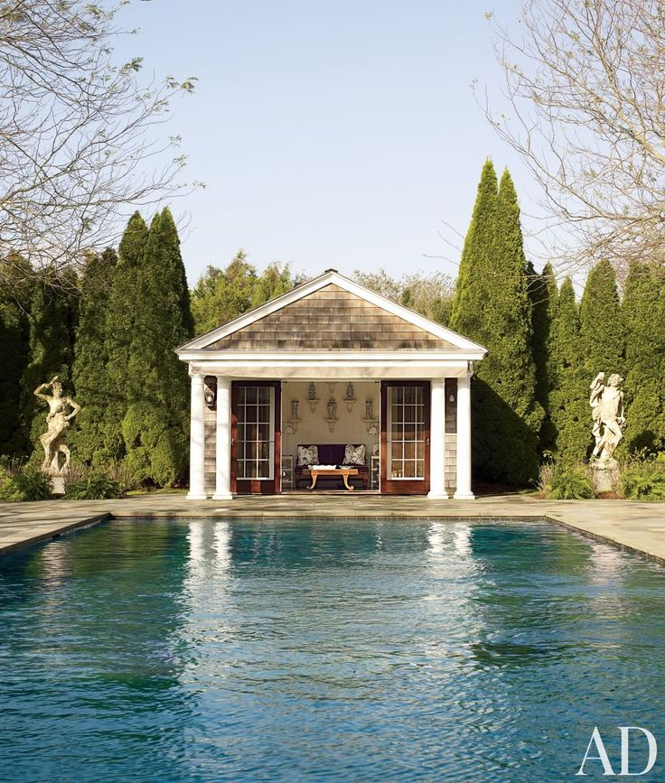 two italian stone statues watch over the outdoor pool at decorator alex papachristidiss hamptons home