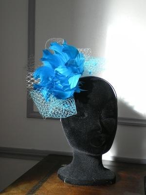 Frimas bleuté, serre-tête garni d'une fleur de plumes turquoises et voilette, 82 € – à Chez les Chapeaux de Ségo .