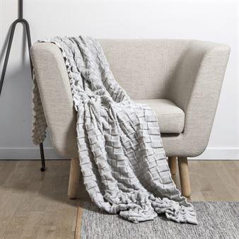 Det strikkede pleddet Curly fra Design House Stockholm har et unikt design og et uttrykk som skiller seg ut fra andre tepper og pledd. Det er designet av Margot Barolo og Ulrika Mårtensson og har et tredimensjonalt mønster som kom til etter at man hadde programmert symaskinen til å sy