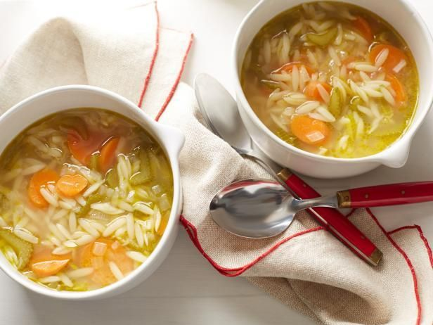 Vegetable Noodle Soup  2 tablespoons extra-virgin olive oil 1 rib celery, sliced (about 1 cup) 1 medium carrot, sliced (about 3/4 cup) 1 clove garlic, smashed 1/4 medium onion, about 1/2 cup 1/4 teaspoon kosher salt 1/3 cup orzo or other small pasta or egg noodles or broken up spaghetti 4 cups low-sodium chicken broth (1-quart box, or 2 cans) Small handful fresh parsley leaves, basil or dill, chopped (about 2 tablespoons) 1/2 lemon