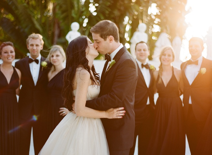 Ozzy Garcia, Photographer - I really like the inclusion of the bridal party in this kiss photo, and the quality of light